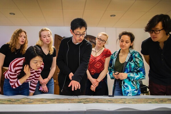 Seven students gathered together looking at a painted Chinese scroll unrolled on a table.
