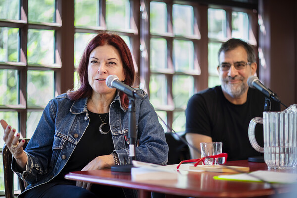 Rosanne Cash speaking at microphone at table with professor Al Filreis looking at her and smiling.