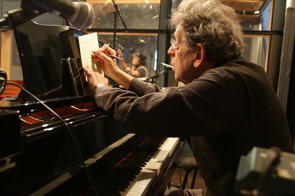 Philip Glass writing at piano