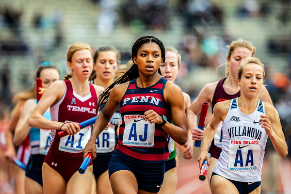 Nia Akins runs with a baton in her hand at the 2019 Penn Relays.