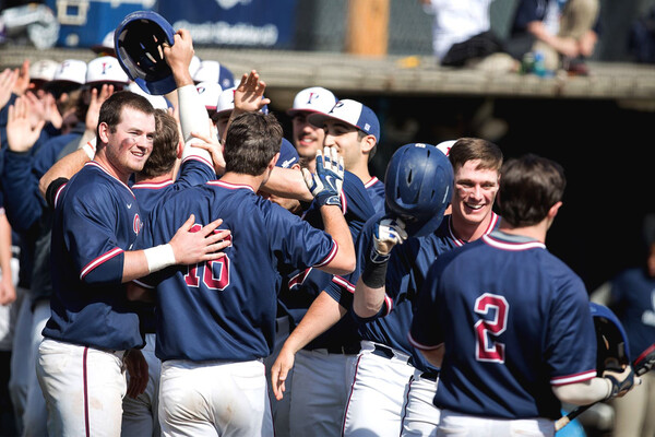 Players on the Penn baseball team celebrate and high five in a group.