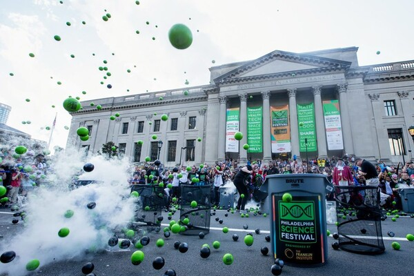 a large group of people in front of the Franklin Institute building with a science demonstration (with smoke and the aftermath of an explosion that caused colored balls to fly into the air) in the foreground