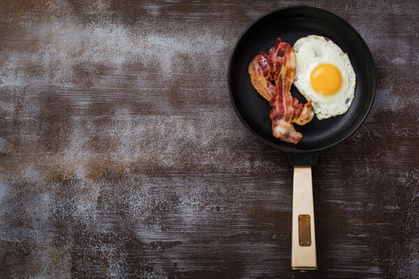 skillet on a table surface with one fried egg and two strips of bacon