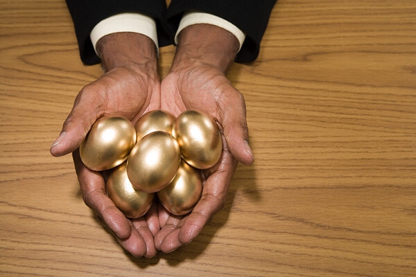 outstretched hand holding several golden eggs on a table