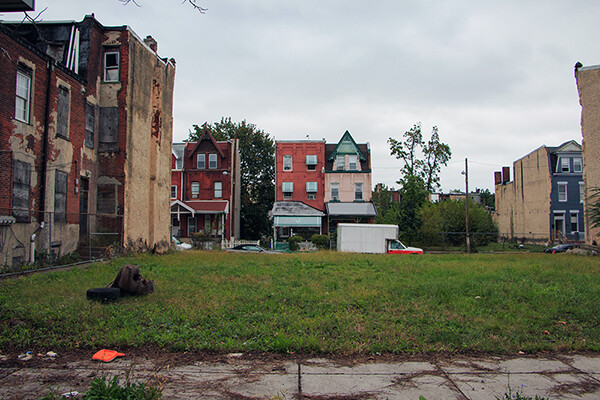 A vacant lot between rowhouses in Philadelphia