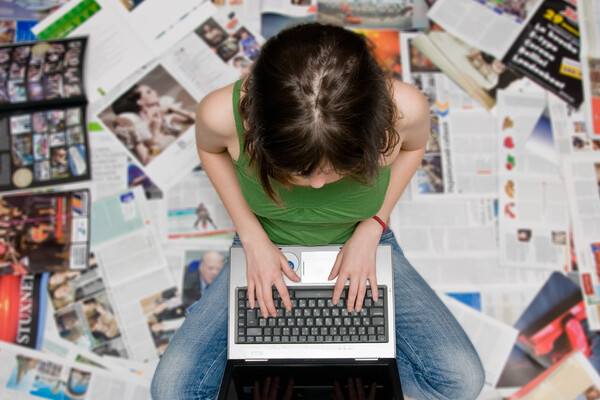 a person sitting on a stack of open magazines and newspapers working on a laptop