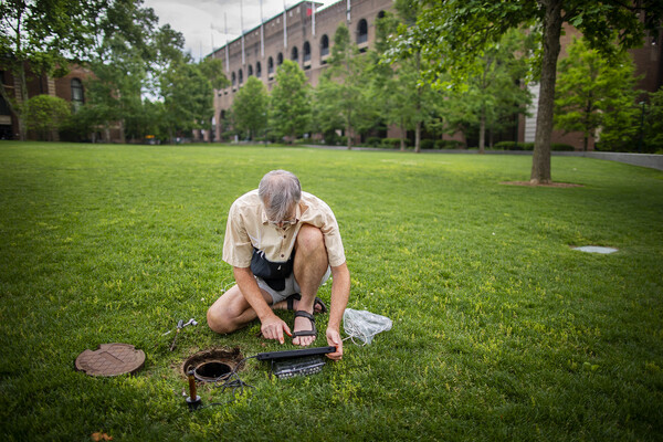 A scientist kneeling on a lawn checks a well using electronic monitoring equipment