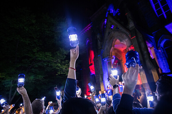 The crowd of students hold lanterns aloft in the night sky in front of College Hall.
