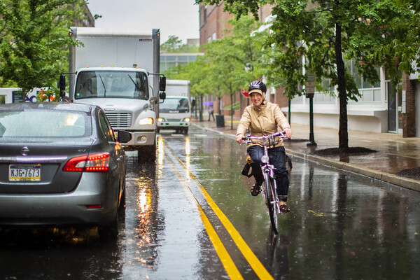 Bike rider in the rain coming down a street with cars and trucks in the opposite lane