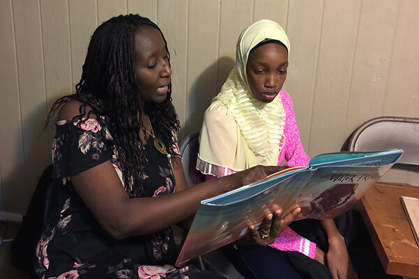 Aminata Sy sits with student reading a book to them.