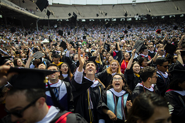 Graduates toss their caps in the air.