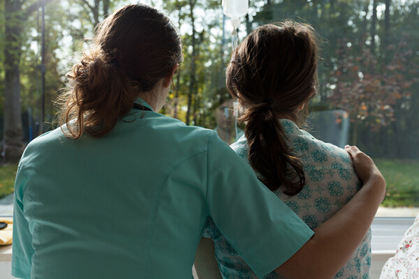 A hospital worker with arm around a patient seen from behind as they look out the window.