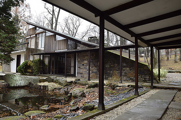 George Nakashima's Arts Building, the facade of the house with a portico and a small pond surrounded by stones.