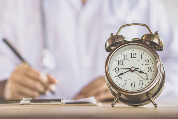 alarm clock in foreground with a doctor writing on a paper at a desk holding a pen in the background