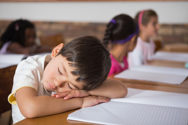 Child in a white shirt sleep on a paper-covered desk in a classroom, with three students in the background.