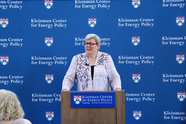 "Rachel Kyte stands at a podium speaking, the sign on the podium reads ""Kleinman Center for Energy Policy."""