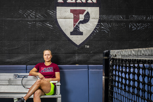 Iuliia Bryzgalova poses on a bench with her racket at the tennis courts at Penn Park.