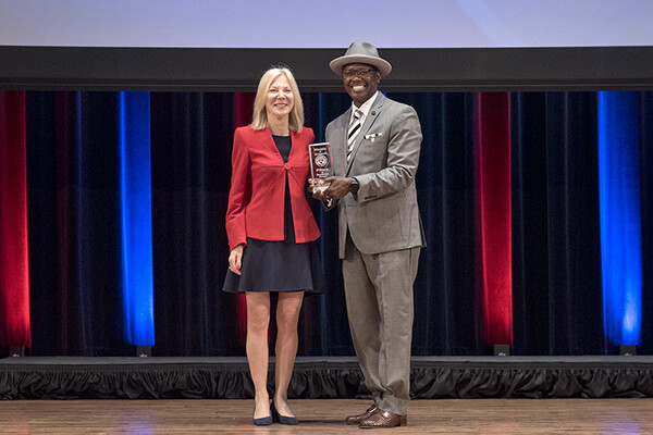 Amy Gutmann and Lorenzo Jackson on stage, Jackson holds an award.