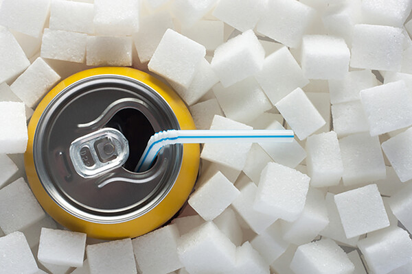 soda can with straw surrounded by a pile of sugar cubes