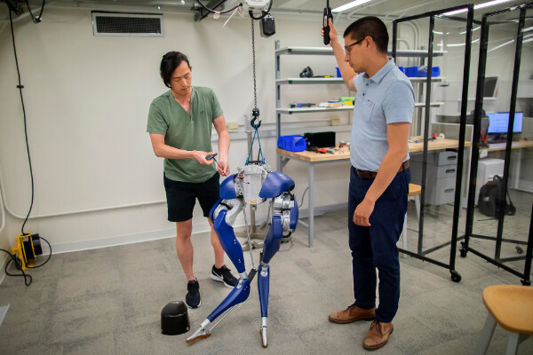 two people working on a set of robotic legs