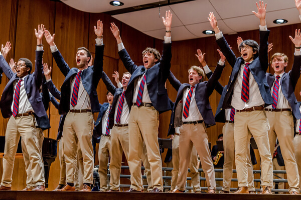 Three lines of students on stage dressed in blue blazers, khaki pants, and red-and-blue-striped ties singing with their arms over their heads.