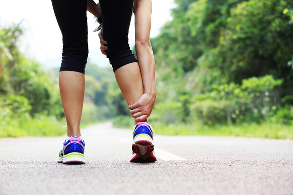 A stock photo of a woman holding her ankle while out for a jog on a road.