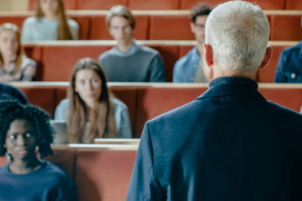 person facing a classroom auditorium with back to camera