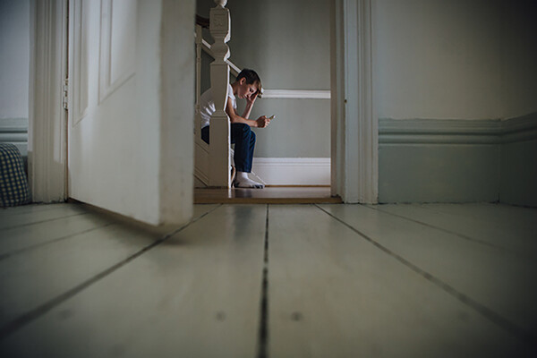 open door with young person sitting on bottom stair of a staircase in background, looking down at a phone in hand.
