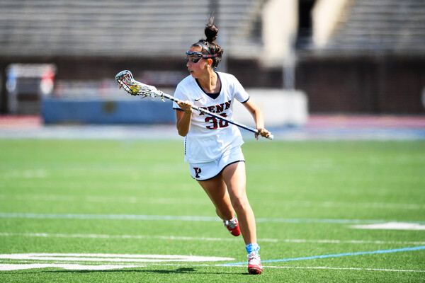 Michaela McMahon of the women's lacrosse runs up the field holding her stick.