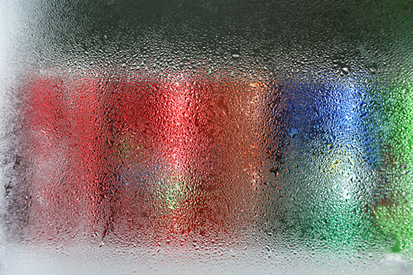 cans of soda on a cooler shelf with condensation on the glass of the door.