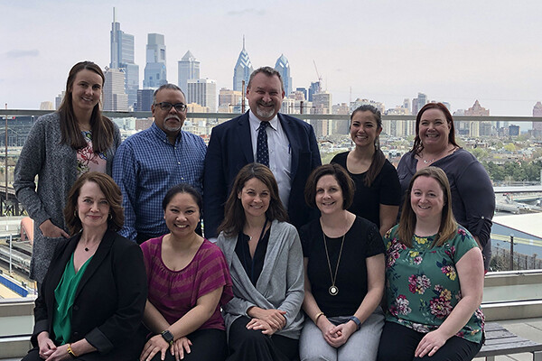 Team portrait of OncoLink staff on a rooftop with Philadelphia skyline in background