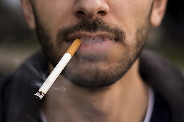 Closeup of bottom third of a young person's face smoking a cigarette