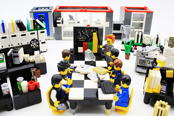 Lego figurines seated at a toy desk made to look like a business office