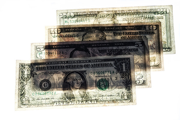 Four semi-transparent paper U.S. bills fanned out flat.