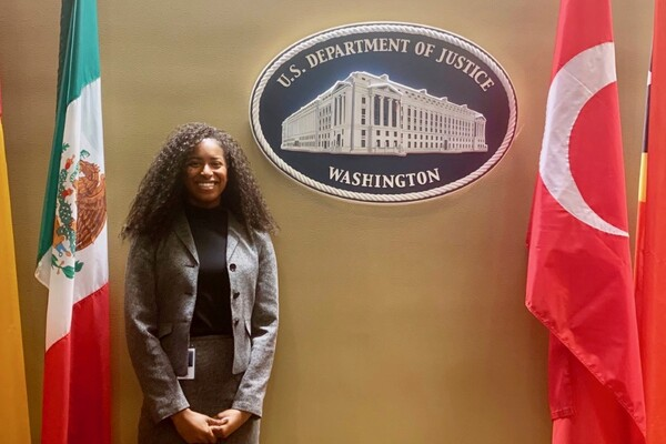 Student standing in front of plaque that says U.S. Department of Justice Washington, and flanked by two flags.