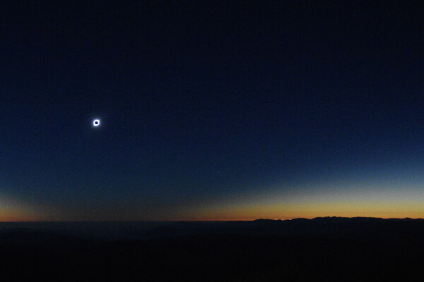 the sun covered by the moon during an eclipse, set against a darkening dusky sky with a black flat horizon in the foreground