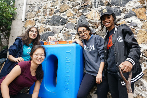 Four smiling students posing by a blue container with a level on top of it