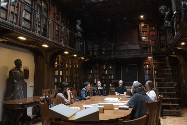 A group of people sitting around a rectangular wooden table on the bottom floor of a two-story room in a library adorned with books and busts.
