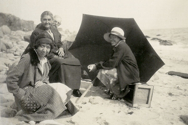 Gladys Tantaquidgeon seated on a beach with four other people and a black umbrella on the ground.