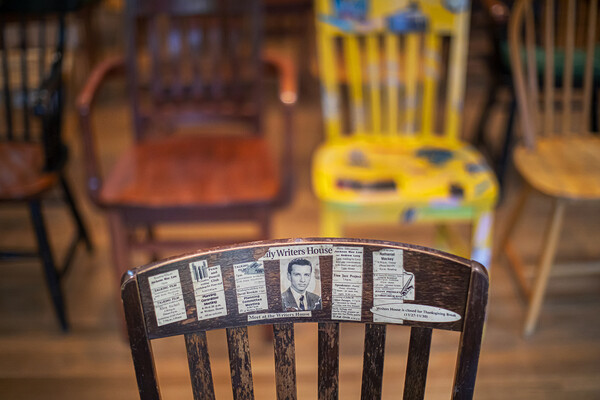 Top of the back of a wooden chair with newspaper articles and photos pasted on.