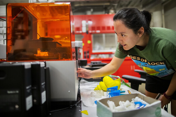 Scientist looks at a 3D printer in a scientific lab