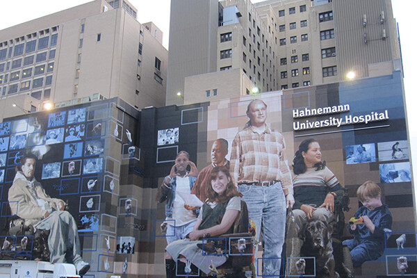Front facade of Hahnemann Hospital with large murals of patients standing and sitting and in wheelchairs and a toddler.