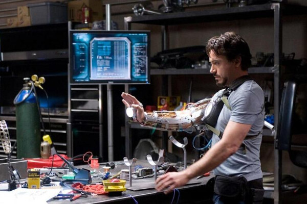 Film still of Robert Downey Jr.'s Iron Man character standing at a work table full of tools trying on a robotic-looking arm.