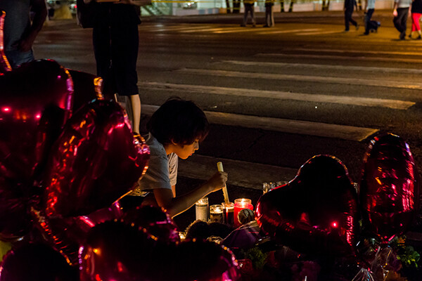 young child kneeling on ground lighting a candle surrounded by heart balloons at night, at a vigil for a mass shooting.