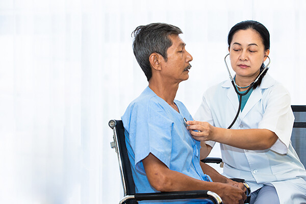 Prostate cancer patient sits in wheelchair while nurse listens to chest with a stethoscope.