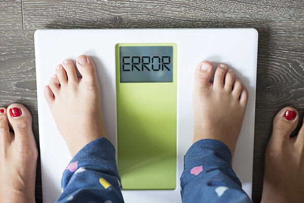 small child stands on scale with error message with adult's feet alongside the scale, symbolizing early weight stigma