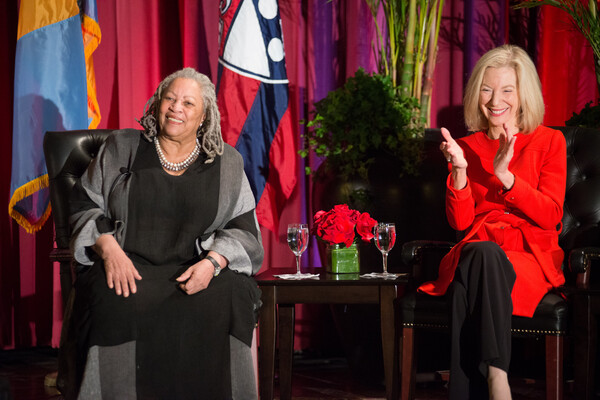 Amy Gutmann and Toni Morrison seated on stage with flags behind them