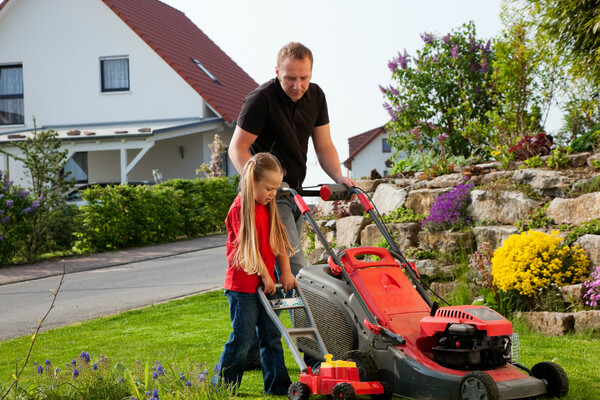 Parent teaching child how to mow grass