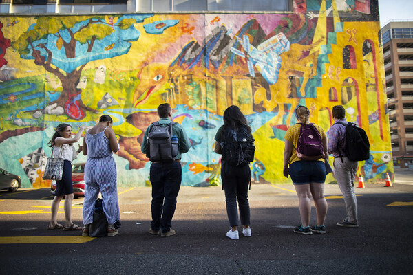 Six people standing in a parking lot looking at a colorful mural on the wall of a building.