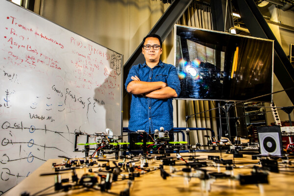 david saldana behind a table of his modular flying robots in front of a white board of equations and a TV screen